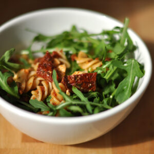 Nudelsalat mit getrockneten Tomaten, Mozzarella und Rucola