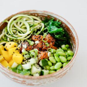 Poké Bowl mit Lachs, Wakame, Edamame, Mango, Gurke und Zucchini